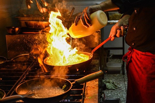 A person cooking food in a pan on a stove top oven