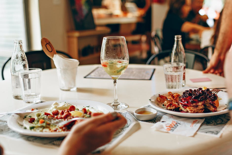 A plate of food and glasses of wine on a table