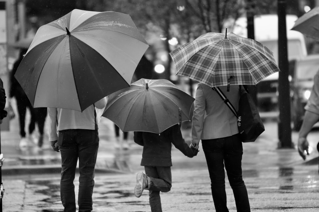 A group of people walking in the rain holding an umbrella